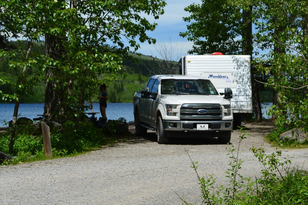 RV and pickup truck in campsite backing onto lake