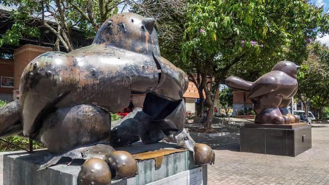 Vorne die gesprengte Statue als Erinnerung an das Attentat von 1995, hinten die neue Friedenstaube.