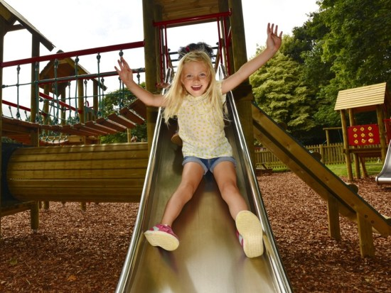 Slides for parks and playgrounds- picture shows a girl sliding down