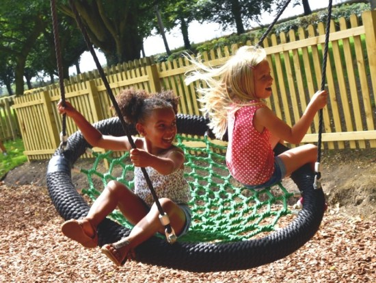 Children on plying on a basket / nest swing