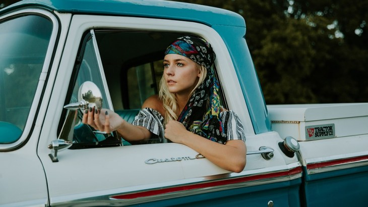 Beautiful woman wearing a bandanna driving a classic car