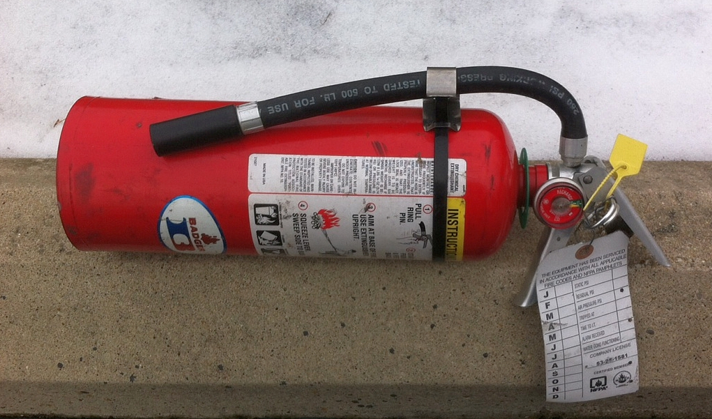 Keep the hose attached to the body just like this. Spray and then thrust with the bottom of the extinguisher's body.