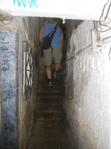 "Walking on a sidewalk between favela houses. Most favelas have no roads and residents walk in narrow passageways like this to get to their ""house."""