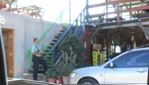 Guard carrying a slung pistol gripped shotgun outside of San Salvador restaurant.