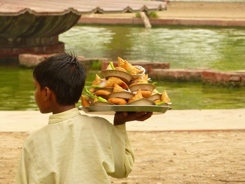 Indian boy selling cake