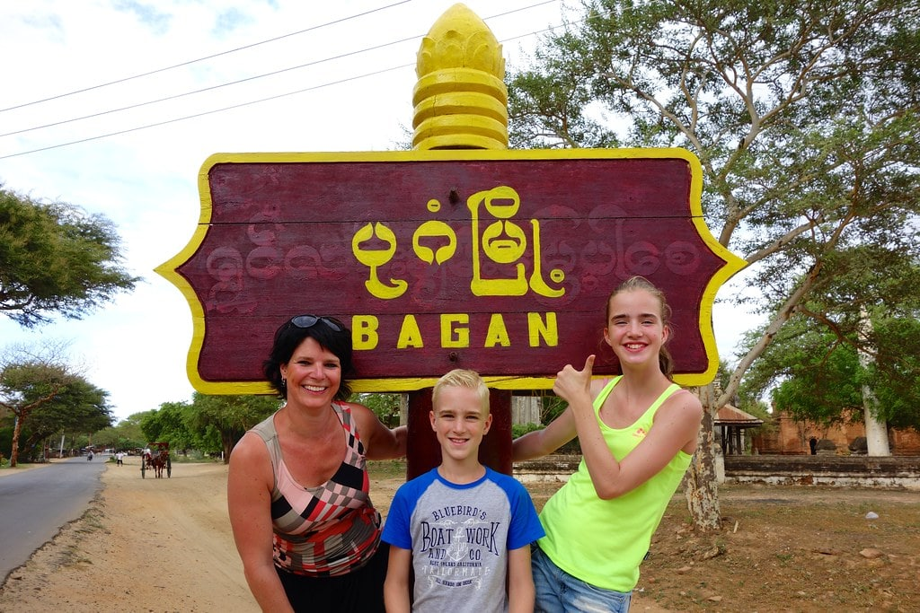 Family in front on Bagan village sign