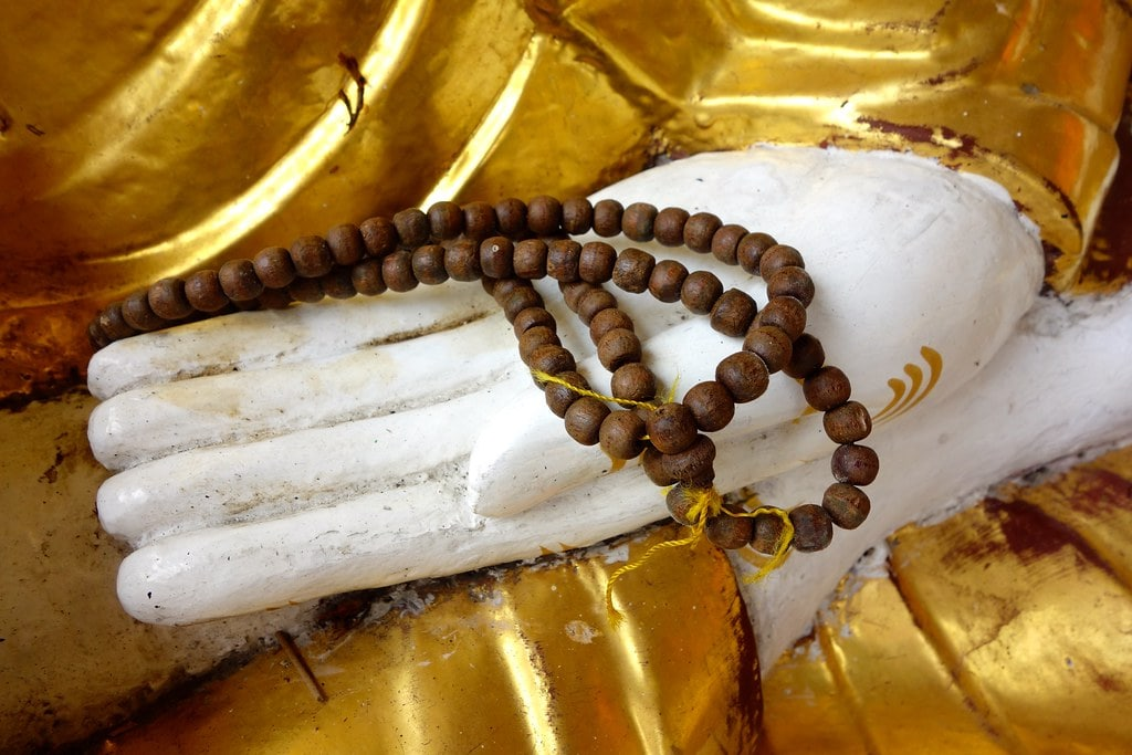 Prayer beads in hand of Buddha