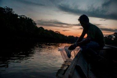Dagoberto pasa los alevinos de arahuana de las redes a bolsas de plástico. Estas bolsas sirven para trasladar los alevinos, con cuidado y sin afectarlos, hacia el centro de acopio de la comunidad.