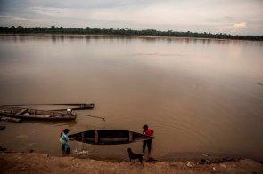 Dos comuneros sacan el agua de la canoa en las orillas del gran río Putumayo. El río es el centro de la existencia de los comuneros de Tres Esquinas.