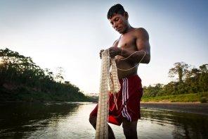 """Hilbert Ruiz Gómez, asheninka de la CN Dulce Gloria pesca con la tarrafa. """"Todos los días se pesca, en nuestra casa nunca falta el pescado"""". El río Yurúa es conocido por la cantidad de peces que produce, al punto que no es difícil encontrar grandes bagres como zúngaros y saltones que superan los 100 kilos."""