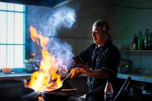 En la cocina de un restaurante en Paita, el cheff prepara un plato de mariscos que requiere un poco de fuego.