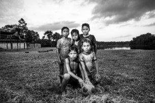 Un grupo de niños descansa después de jugar fútbol en el barro.