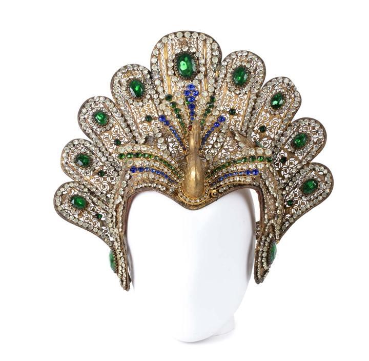 Lotto 181. A. CORBELLA (MILANO), TIARA PER L'AIDA, Anni '30. Rara tiara con pavone, metallo dorato, strass incolori, blu e verde smeraldo. Circonferenza 55 cm. Grado condizione B. Courtesy Bertolami Fine Art
