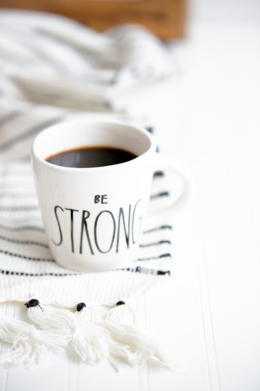 White coffee cup sitting on a striped rug that says be strong.