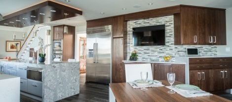 """View of the stand desk and TV area. All counter tops have waterfall edges. The island top is 4"""" thick. Island cabinets have a high-gloss automotive finish."""