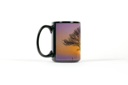 Left view of black mug with a tree silhouetted by a sunset
