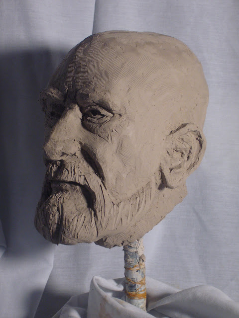 Head sculpture of an older man in clay three quarters view by Adam Miconi
