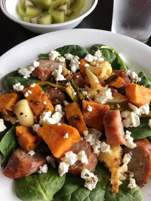 A white plate with Roasted Veggie Sausage Salad containing spinach, sausage, sweet potatoes, garlic, and feta cheese