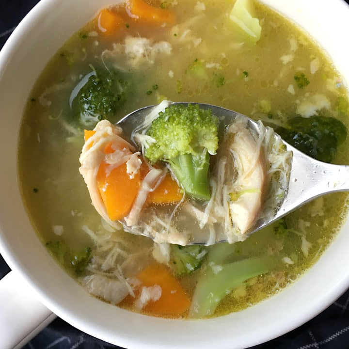 Close-up of a spoonful of broccoli, carrots, and shredded chicken over a white mug of chicken soup
