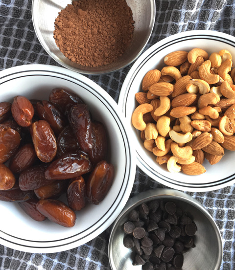 Bowls of dates, cocoa, nuts, and chocolate chips for Chocolate Chip Date Nut Bars