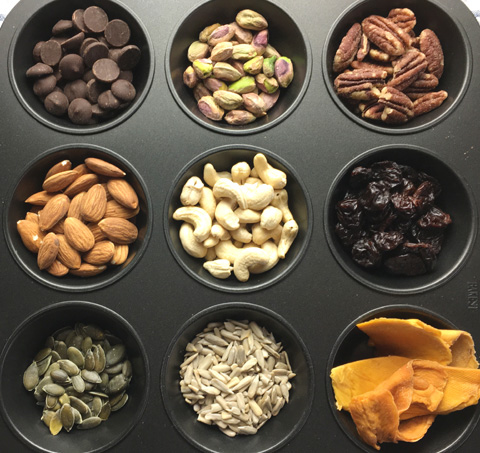 A muffin tin containing nuts, dried fruits, and seeds for DIY Salty & Sweet Trail Mix