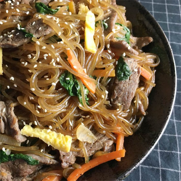A dark round bowl containing brown noodles, carrots, eggs, beef, and greens, topped with sesame seeds