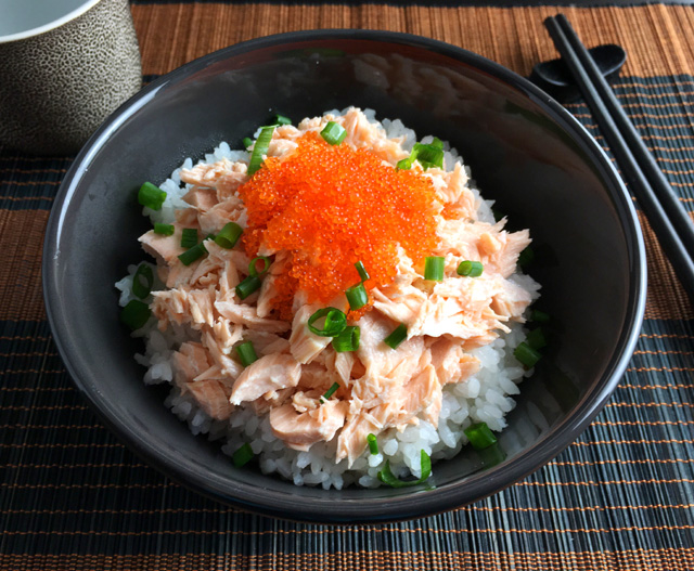 A Poached Salmon Tobiko Bowl on a brown and black bamboo platemat with chopsticks and a teacup