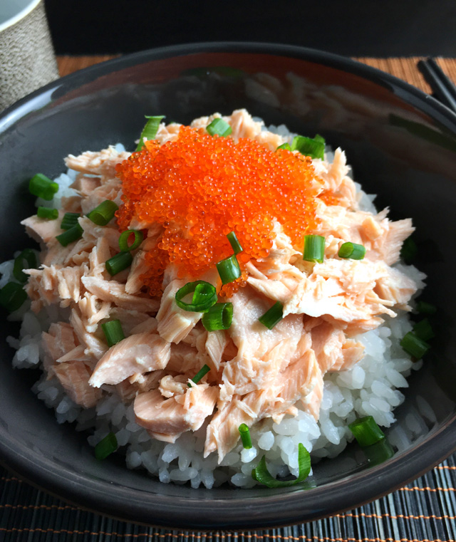 Close-up of a Poached Salmon Tobiko Bowl containing white rice, salmon, orange fish eggs, and green onions