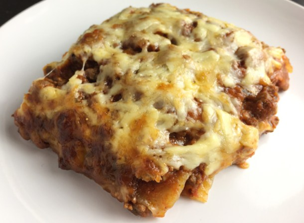 A white plate containing a piece of Cheesy Bolognese Lasagna