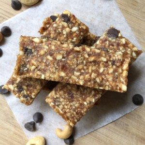 A stack of cashew date bars on parchment