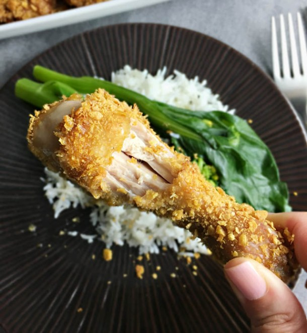 Fingers holding a cornflakes chicken drumstick with a bite taken out of it, a round plate with rice and green vegetables in the background