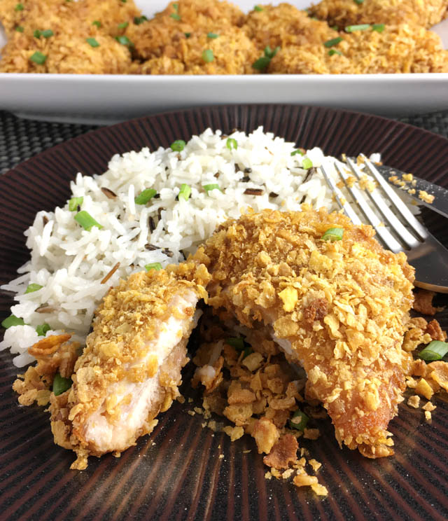 A round brown plate containing white rice and a cut piece of cornflakes chicken