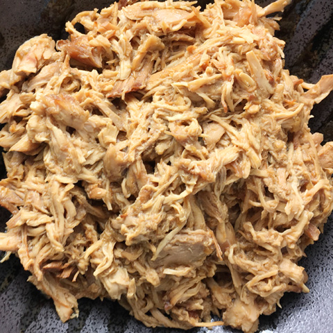 A black bowl of pulled chicken