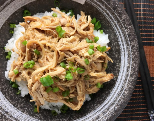 A bowl of Slow Cooker Teriyaki Pulled Chicken on white rice with green onions