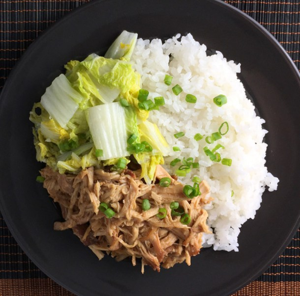 A black plate of shredded chicken with white rice, napa cabbage and chopped green onion