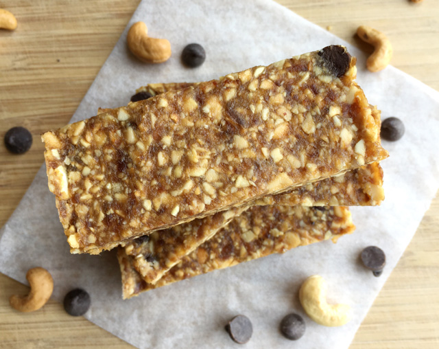 Looking down on a stack of Chocolate Chip Cashew Date Bars surrounded by chocolate chips and whole cashews