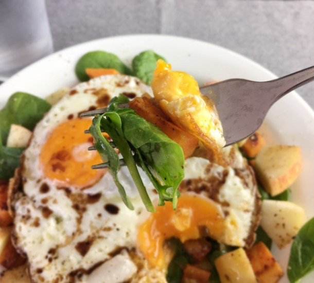A forkful of spinach, fried egg, and roasted vegetable from Crispy Fried Eggs Over Veggies