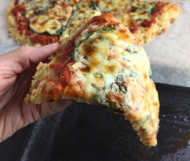 A hand holding up a slice of Rice Crust Pizza
