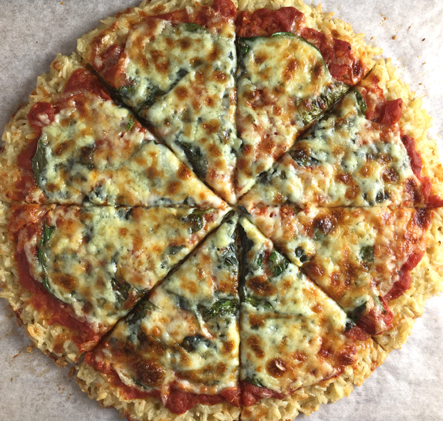 A whole Rice Crust Pizza made of rice, tomato sauce, spinach, and cheese