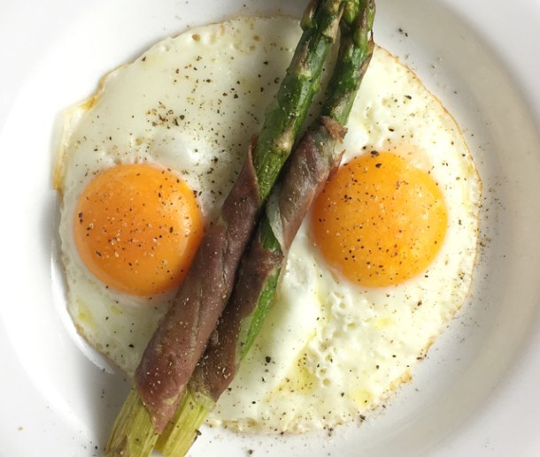 Prosciutto Wrapped Asparagus on a white plate with two fried eggs