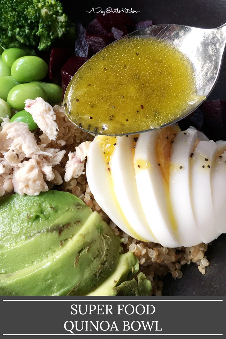 A spoonful for orange dressing being drizzled over a quinoa bowl, the words super food quinoa bowl on the bottom