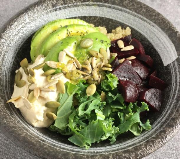 Super Food Quinoa Bowl containing quinoa, avocado, hummus, kale, beets, and sunflower and pumpkin seeds