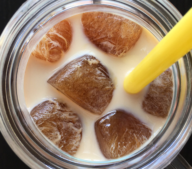 Looking into a glass filled with milk and Cold Brewed Coffee Ice Cubes and a yellow straw