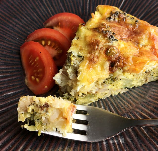 Red tomato wedges and a wedge of roasted vegetable quiche on a brown plate with a forkful of quiche