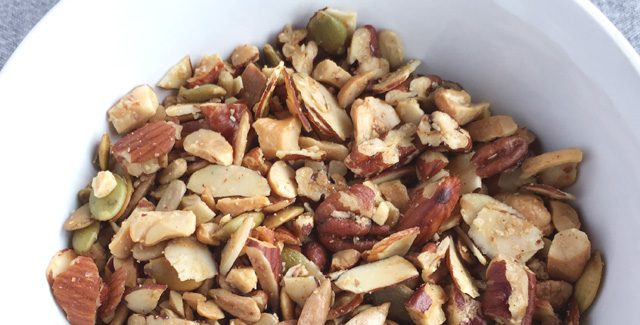Close-up of a white bowl of Easy Grain Free Nutty Granola with almonds, pecans, cashews, sesame seeds, and pumpkin seeds