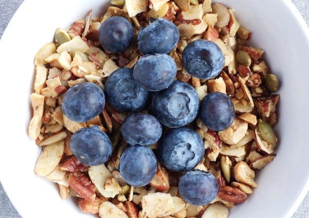 A white bowl of Easy Grain Free Nutty Granola topped with blueberries