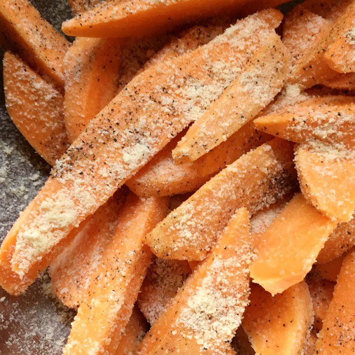 Orange sweet potato wedges coated with black pepper and dry Parmesan cheese