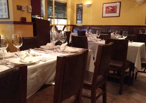 Tables with place settings and wine glasses and chairs in the dining room at La Pampa