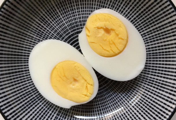 A hard cooked egg cut in half on a round plate. Cook Eggs In A Rice Cooker