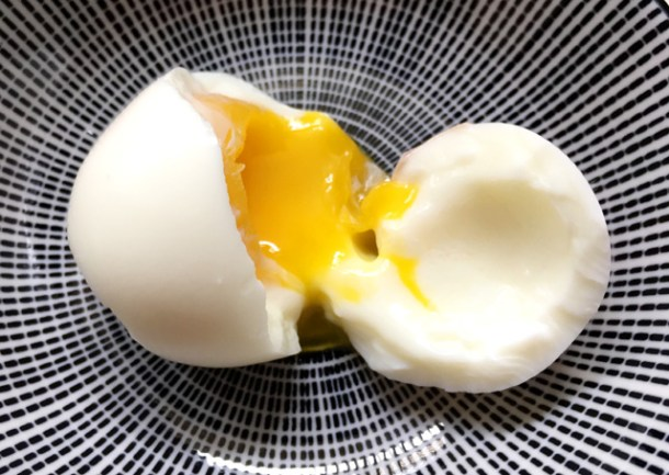 An open soft-cooked egg on a plate. Cook Eggs In A Rice Cooker